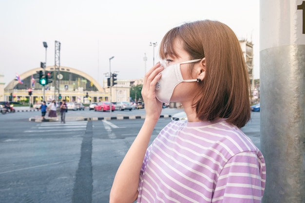 Asian woman wearing the n95 respiratory protection mask against air pollution at road and traffic in bangkok