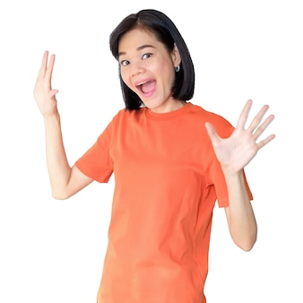 An asian woman wearing an orange shirt poses with a happy wow face.
