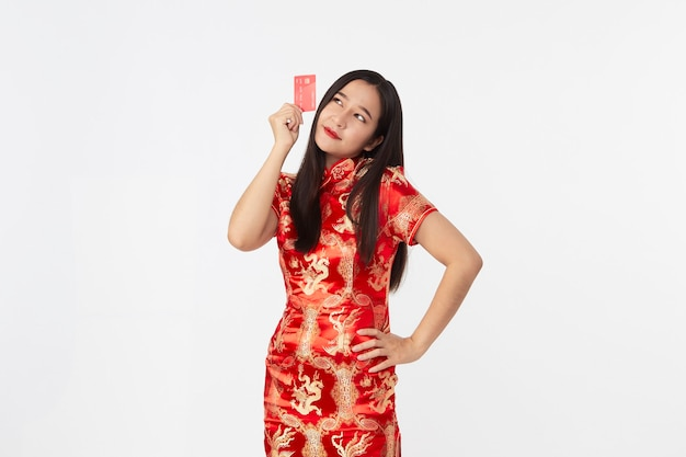 Asian woman wearing oriental qipao dress showing red credit card in hand  in light gray isolated studio surface
