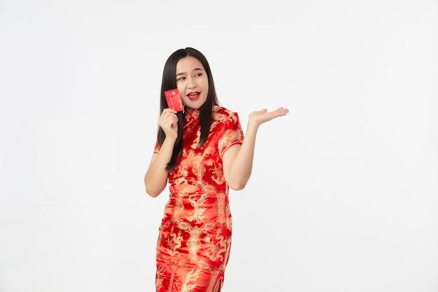 ライトグレーの隔離されたスタジオの表面で手に赤いクレジットカードを示す東洋のチャイナドレスを着ているアジアの女性