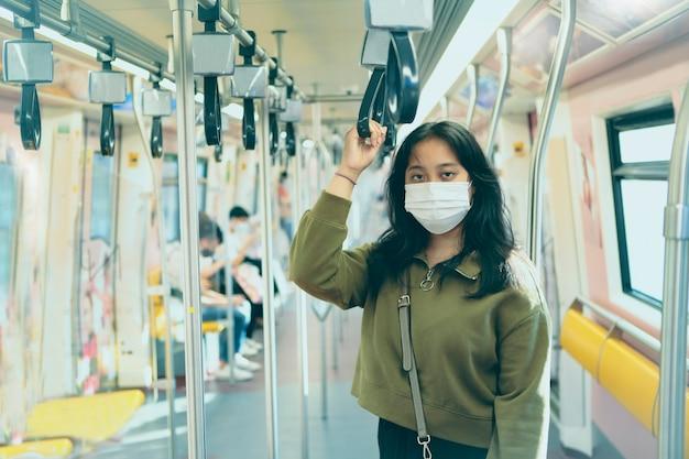 都市の空の列車に立っている保護マスクを身に着けているアジアの女性