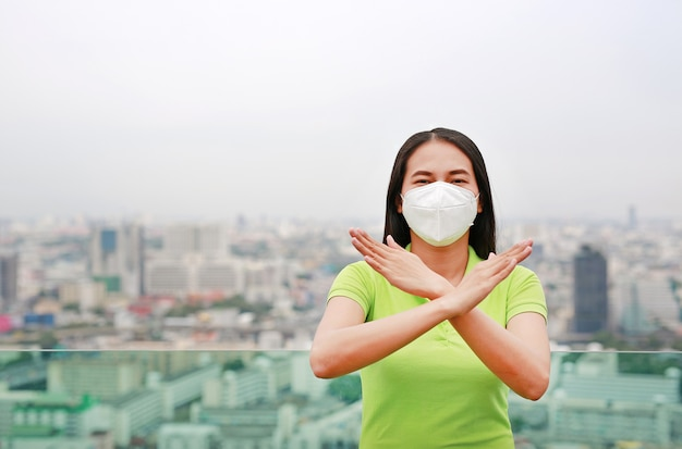 Asian woman wearing a protection mask with making x sign