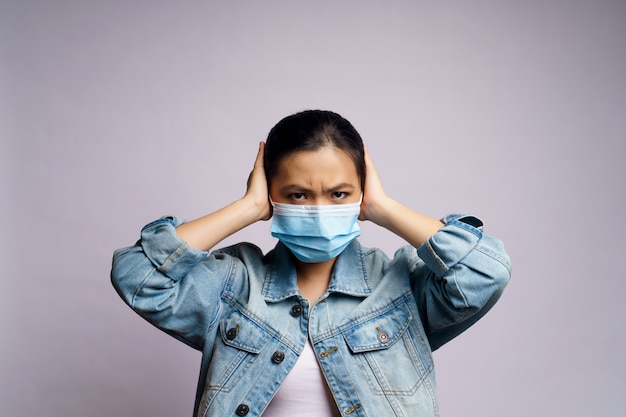 Asian woman wearing protective face mask and covering her ears by hands isolated.