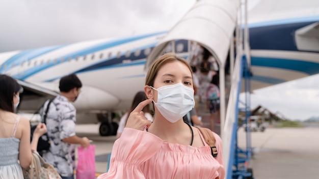 Covid-19ウイルスのパンデミック時に保護フェイスマスクを着用しているアジア人女性は、飛行機に入る階段に歩いて行き、空港のターミナルの外に駐車します。