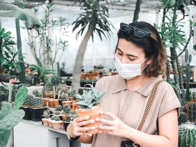 テラコッタポットで小さなサボテンを探して防護マスクを身に着けているアジアの女性