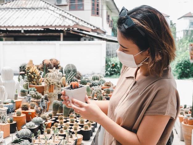 白い鍋に小さなサボテンを探して防護マスクを身に着けているアジアの女性
