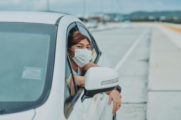コロナウイルスcovid-19屋外門限パンデミック中に車から降りる前に保護フェイスマスク保護安全を身に着けているアジアの女性