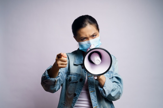 Asian woman wearing protective face mask shouting with megaphone isolated.