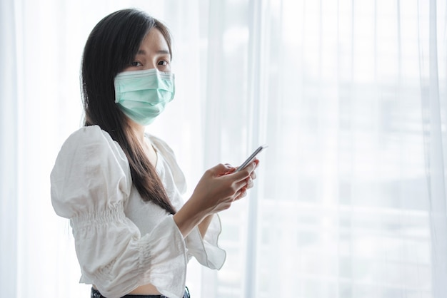 Asian woman wearing protective face mask and using mobile smartphone