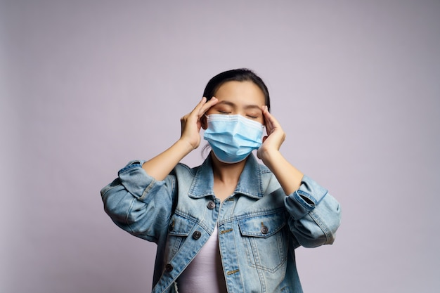 Asian woman wearing protective face mask was sick with headache isolated.