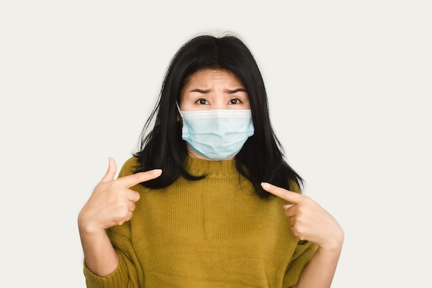 자신을 가리키는 보호 마스크 손을 입고 아시아 여자