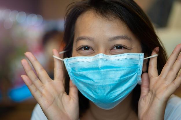 ウイルスcovid-19パンデミックを防ぐために彼女の顔に保護マスクを身に着けているアジアの女性。