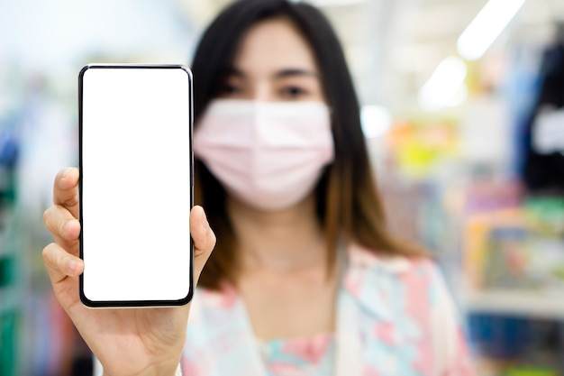 携帯電話を示す保護マスクを身に着けているアジアの女性