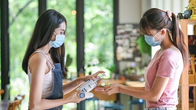 Asian woman wearing protective mask using alcohol antiseptic gel prevent outbreak of covid-19 in cafe