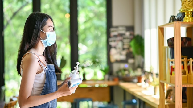 アルコール消毒ジェルを使用して保護マスクを着用しているアジアの女性は、カフェでcovid-19の発生を防ぎます