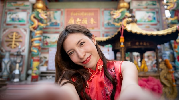 Asian woman wearing red cheongsam dress at chinese shrine. chinese new year concept.
