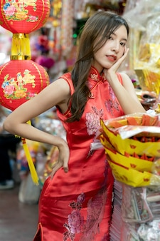 Asian woman wearing red cheongsam dress shopping at market for chinese new year.