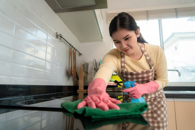 Asian woman wearing rubber protective pink gloves, holding rag and spray.