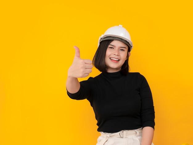 アジアの女性の安全帽子をかぶっているとサインを親指を表示
