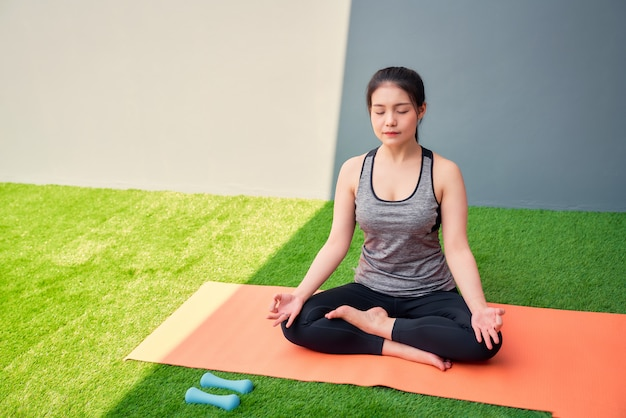 Asian woman wearing sportswear practicing yoga on orange mat on green grass. wellness concept.
