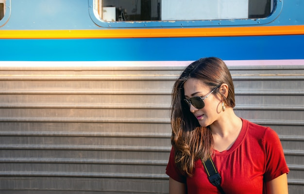 Asian woman wearing sunglasses with train background