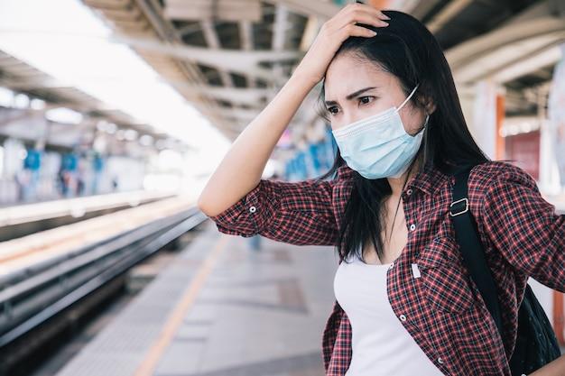 新しいコロナウイルスまたはコロナウイルス病に対するサージカルフェイスマスクを身に着けているアジアの女性公共の駅でコビッド仕事をするのに真面目で遅い社会的距離