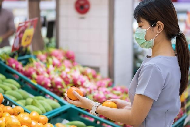 外科用フェイスマスクを着用し、スーパーマーケットでオレンジ色の果物を保持しているアジアの女性