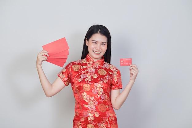 Азиатская женщина в традиционном платье ципао cheongsam, показывающем кредитную карту и красные конверты для китайских новогодних покупок.
