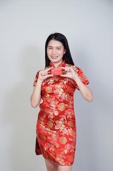 Азиатская женщина в традиционном платье cheongsam qipao показывает кредитную карту для китайских новогодних покупок.