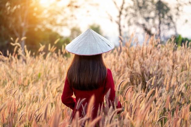 Азиатская женщина нося традиционную культуру вьетнама в африканском поле цветка фонтана.