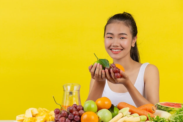 An asian woman wearing a white tank top. both hands held fruit and the table is full of various fruits.