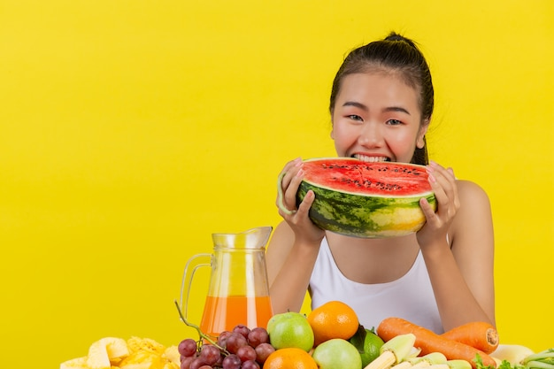 An asian woman wearing a white tank top. both hands hold watermelons and the table is full of various fruits.