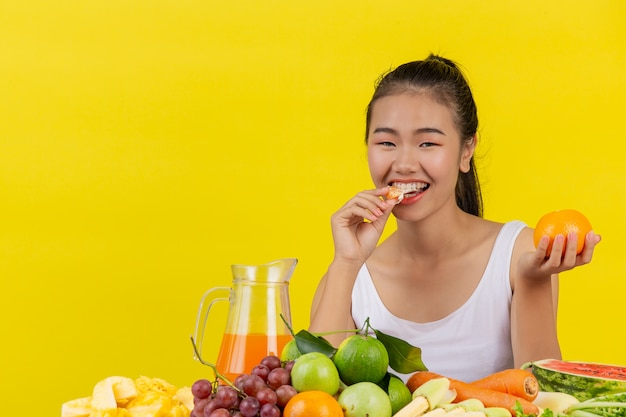 An asian woman wearing a white tank top eating orange and the table is full of various fruits.