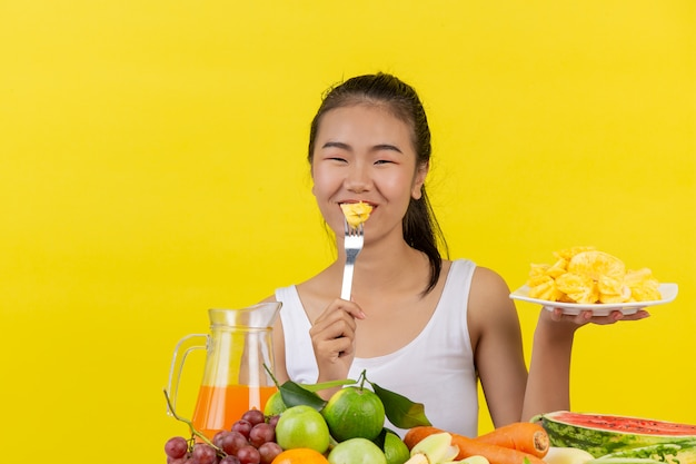 An asian woman wearing a white tank top. eating pineapple and the table is full of various kinds of fruits.