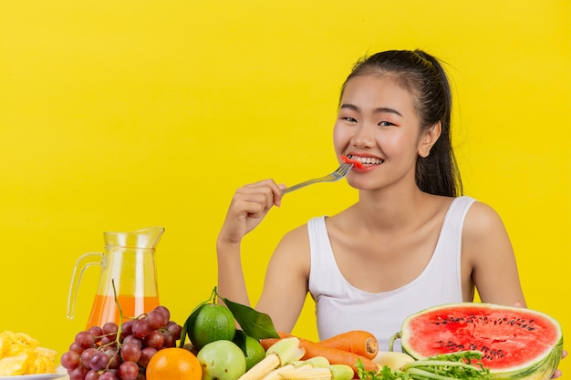 An asian woman wearing a white tank top eating watermelon and the table is full of various fruits.