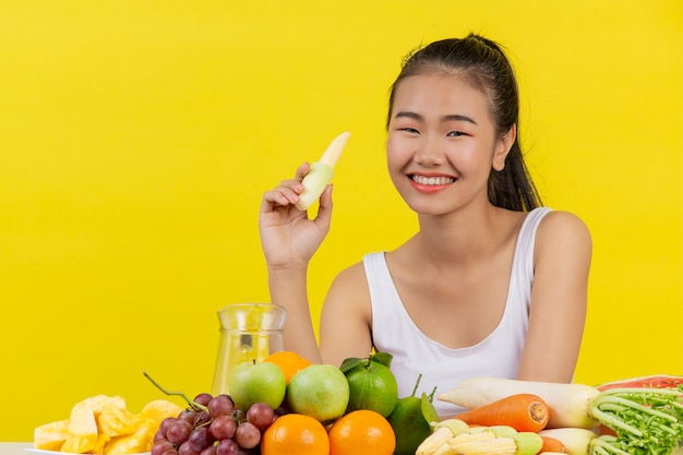 An asian woman wearing a white tank top. hold the baby corn with your right hand. and on the table there are many different fruits.