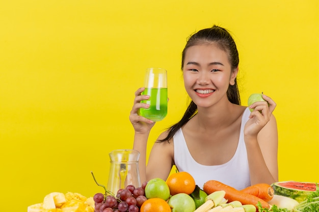 An asian woman wearing a white tank top. holding a glass of apple juice with your right hand holdingapple with the left hand and the table is full of various kinds of fruits.
