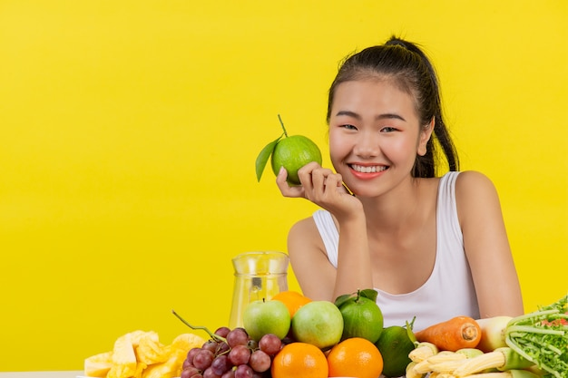 An asian woman wearing a white tank top. holdingorange with the right hand and on the table there are many different fruits.