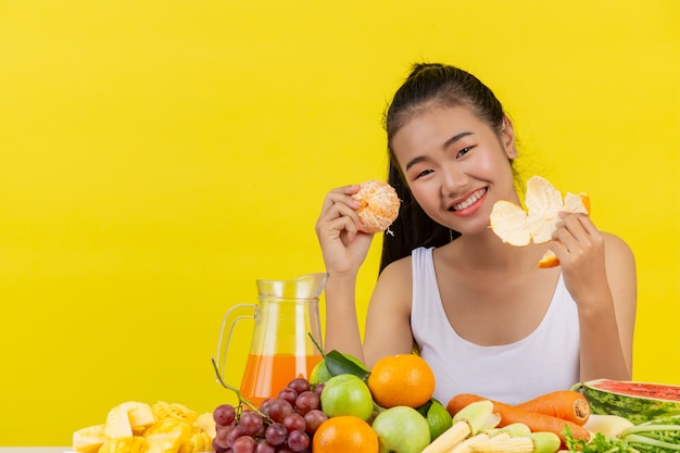 An asian woman wearing a white tank top. i'm peelingorange peel and the table is full of various kinds of fruits.