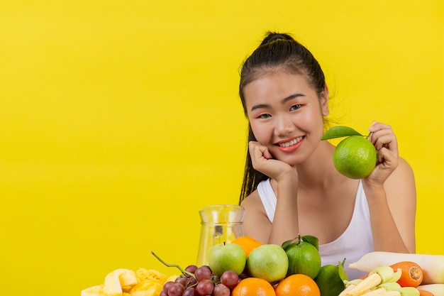 An asian woman wearing a white tank top. the left hand holds a green oranges and the table is full of many kinds of fruits.