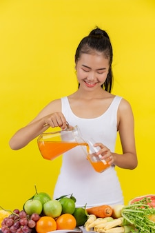 An asian woman wearing a white tank top. pouring orange juice into a glass and on the table there are many fruits.