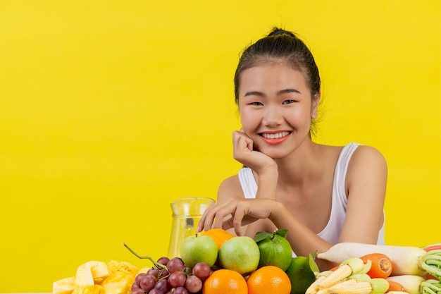 An asian woman wearing a white tank top. the table is full of many kinds of fruits.