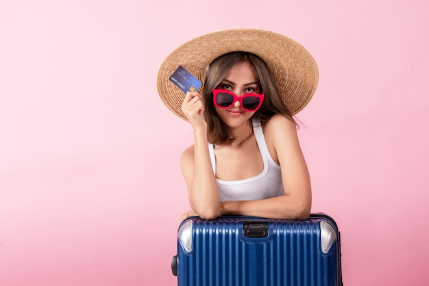 An asian woman wearing a wide-brimmed hat and summer clothes standing with a suitcase she is holding a credit card. isolated on a pink background
