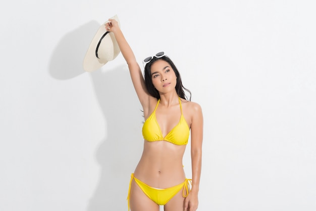 Asian woman wearing a yellow bikini dress in a standing fashion, with a white sunglasses, in a summer fashion at studio shot white background.
