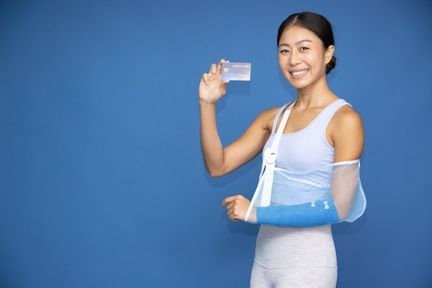 Asian woman wearing yoga or exercise clothes put on a soft splint due to a broken arm using crutches and showing credit card isolated on blue background