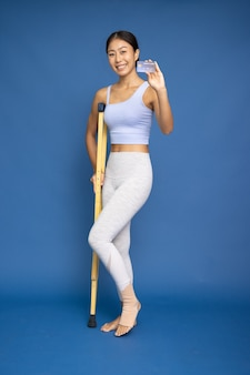 Asian woman wearing yoga or exercise clothes using a crutch and showing credit card on hand isolated on blue background