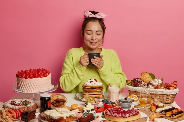 Asian woman wears headband, drinks tea, surrounded with delicious desserts, holds mug, keeps eyes closed, isolated on pink wall. sweet tooth enjoys tasty breakfast.
