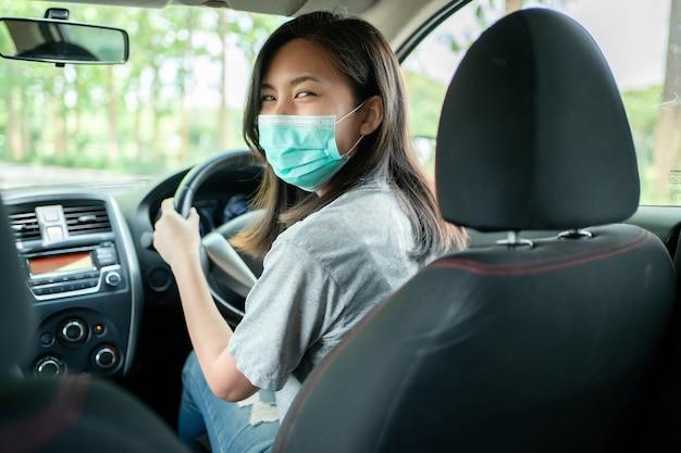 운전 중 코로나 19 예방을 위해 마스크를 쓴 아시아 여성