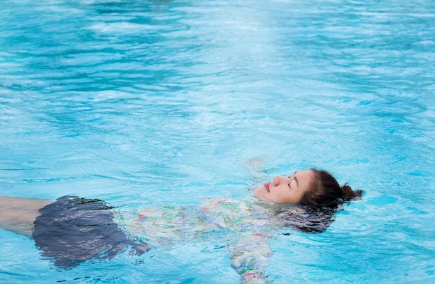 Asian woman wears a swimsuit floating in an outdoor pool with clear blue water on a summer holiday.