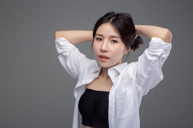The asian woman wears a white shirt and hands touch her hair.